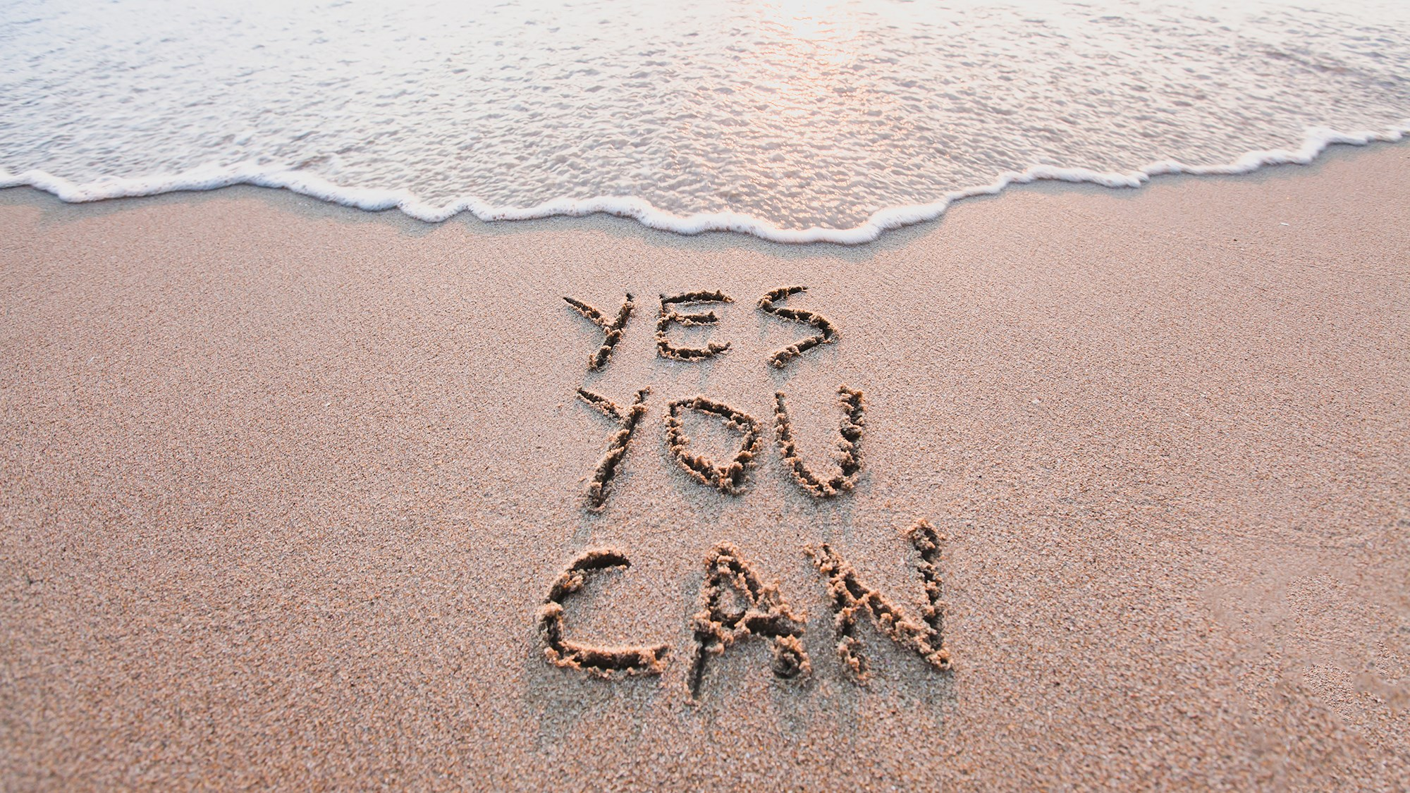 """yes you can"" in den Sand geschrieben"